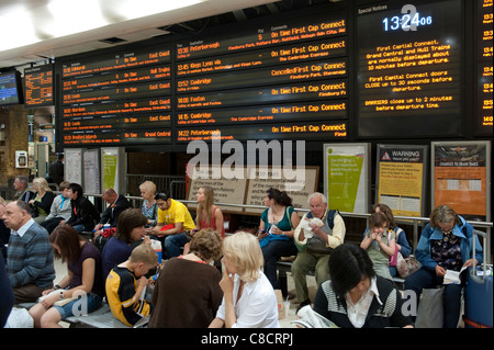 Passengers waiting beneath a passenger information board at Kings Cross railway Station in London. - Stock Photo