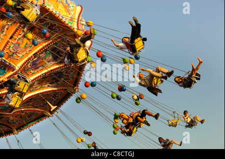 world famous Oktoberfest in Munich, Germany with carousel at evening - Stock Photo