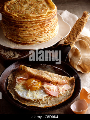 Egg and ham crepe in pan - Stock Photo