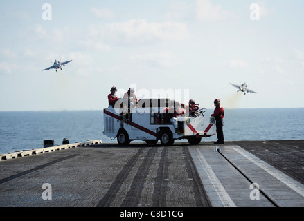 Sailors stand flight deck fire watch as an F/A-18C Hornet assigned to the Warhawks of Strike Fighter Squadron (VFA) - Stock Photo