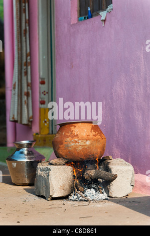 Cooking rice in a metal pot outside on an open fire in a rural indian village.  Andhra Pradesh, India - Stock Photo