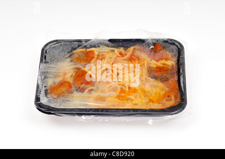 Tray of hot cooked microwave spaghetti and meatballs ready meal with plastic tray & film cover on white background - Stock Photo
