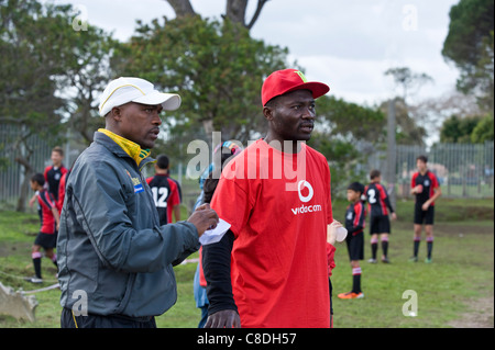 Football coaches watching a match of a youth team in Cape Town South Africa - Stock Photo
