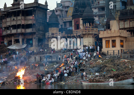 Body bathed in River Ganges at Hindu cremation on funeral pyre at Manikarnika Ghat in Holy City of Varanasi, Benares, - Stock Photo