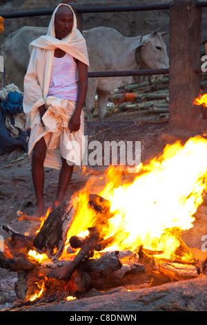 Body burning on funeral pyre at Hindu cremation at Manikarnika crematorium Ghat in Holy City of Varanasi, Benares, - Stock Photo