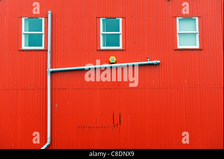 A drainpipe on the side of a red corrugated iron building in Lerwick, Shetland Islands, Scotland. - Stock Photo