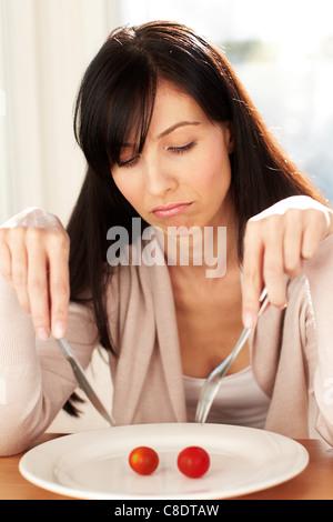 Woman eating tomato - Stock Photo