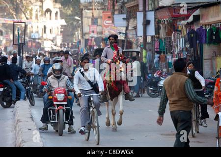 Busy street scene in holy city of Varanasi, Benares, Northern India - Stock Photo