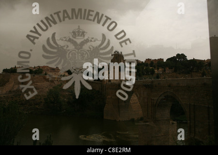 Coat of arms of Toledo on glass with panorama of the city with Puente de San Martin over the Tajo River (Tagus River) - Stock Photo