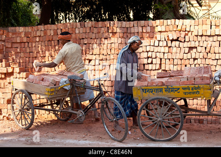 Indian men stacking TATA bricks in the city of Varanasi, Benares, Northern India - Stock Photo