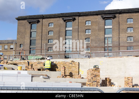 Hard landscaping work being carried out on the banks of the Regents Canal at the Kings Cross development, - Stock Photo