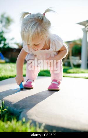 Toddler Girl Writing on Ground with Sidewalk Chalk - Stock Photo