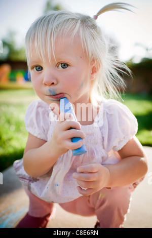 Toddler Girl Drawing on Her Face with Sidewalk Chalk - Stock Photo
