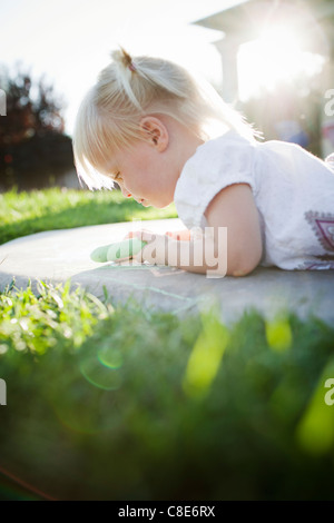 Toddler Girl Laying on Ground Playing with Sidewalk Chalk - Stock Photo