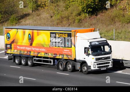 Sainsburys articulated trailer & Fairtrade advertising for bananas including Fairtrade logo behind Volvo hgv lorry - Stock Photo