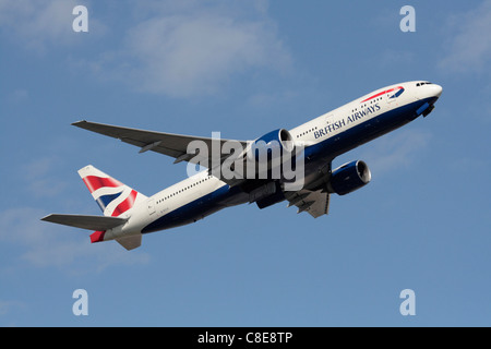 British Airways Boeing 777-200ER widebody passenger jet climbing on departure against a blue sky - Stock Photo