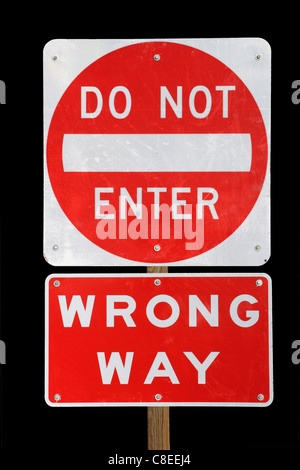 do not enter wrong way red and white road sign on black background - Stock Photo