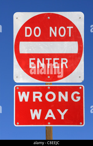do not enter wrong way red and white road sign on blue sky background - Stock Photo