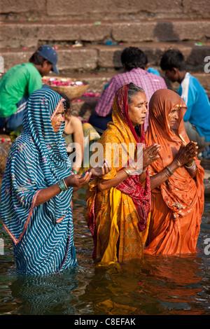 Indian Hindu pilgrims bathing and praying in The Ganges River at Dashashwamedh Ghat in Holy City of Varanasi, India - Stock Photo