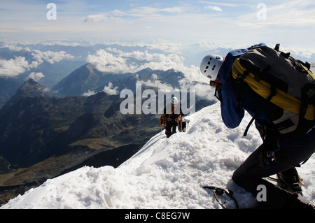 A photographer taking pictures as a team of climbers reach the summit of a peak in the alps - Stock Photo