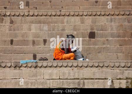 Hindu Sadhu holy man with traditional robe reads on steps of the Ghats in holy city of Varanasi, Benares, Northern - Stock Photo
