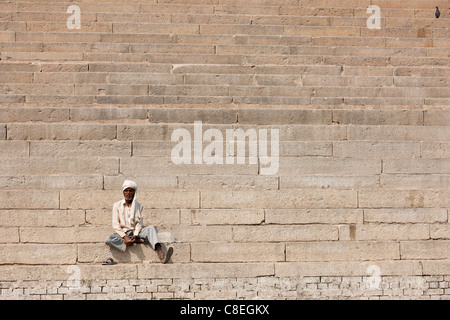 Hindu man sits on steps of Chet Singh Ghat on banks of The Ganges River in holy city of Varanasi, India - Stock Photo