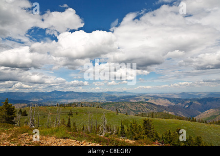 High mountain views with puffy clouds over distant skies - Stock Photo