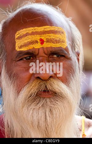 Hindu Sadhu holy man with traditional markings of symbol of Shiva in street in holy city of Varanasi, Benares, Northern - Stock Photo