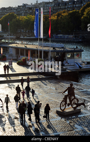 Seine river banks next to the Eiffel Tower at the dusk, barge, tourist ship, biker sculpture - Stock Photo