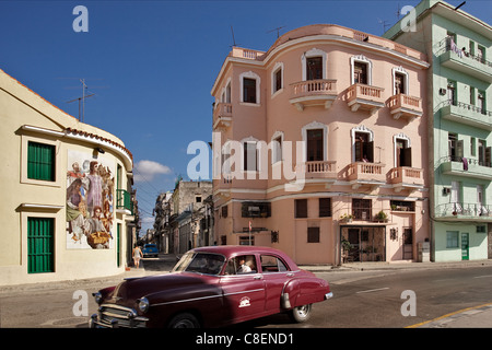 pastel-colored houses in the old havana cuba with red old car in front - Stock Photo