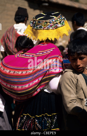 Paucartambo, Peru. Woman wearing traditional dress and carrying a baby in a manta on her back. - Stock Photo