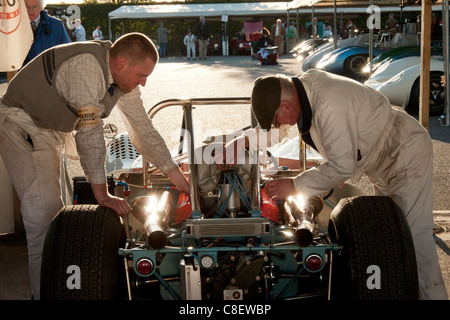 mechanics working on an old formula one car in the paddock at the Goodwood Revival race meeting - Stock Photo