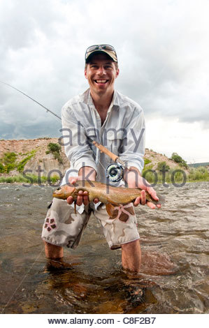 A man in the river with a fishing rod smiles and holds out a trout. - Stock Photo