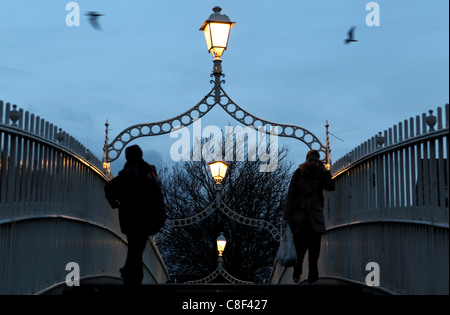 Early morning commuters are silhouetted as they cross over  the river Liffey  on the Ha'penny bridge in Dublin, - Stock Photo
