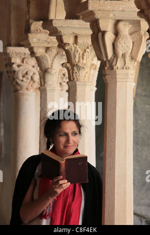 Woman reading the Bible in the Cloister of Saint Sauveur, Aix en Provence, Bouches du Rhone, Provence, France - Stock Photo