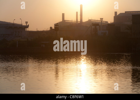 A section of Nile river bank with sun setting in a golden glow behind industrial chimneys reflected in the water, - Stock Photo