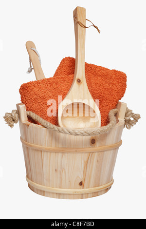 towels on a wooden scoop are in a wooden sauna barrel - Stock Photo