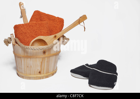 towels on a wooden scoop are in a wooden sauna barrel, alongside are a pair of black slippers - Stock Photo