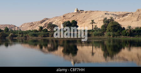 Section of Nile river bank with five men fishing in small boat with trees, a hill with a shrine on top, and perfect - Stock Photo