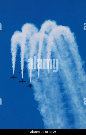 L-39C Albatros aircrafts from the Breitling Jet Team  flying in formation and leaving smoke trails in the sky during - Stock Photo