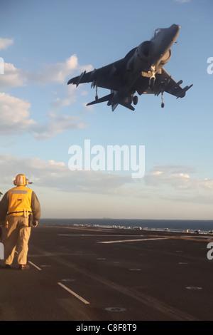 An AV-8B Harrier jet from Marine Aircraft Group 13 lands aboard the USS Bonhomme Richard - Stock Photo