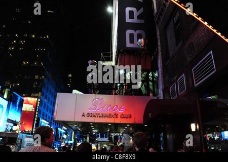 Night-time shot man boy people walking towards red purple neon Lace Gentlemen's Club entrance canopy, 7th Avenue, - Stock Photo