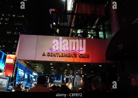 Night-time shot traffic, blue billboards, people walking under purple neon canopy Lace Gentlemen's Club, 7th Avenue, - Stock Photo