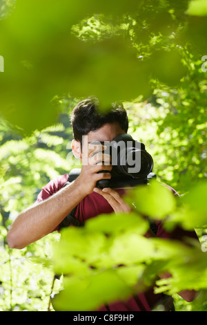 young hispanic man trekking among trees and taking pictures with dslr camera. Vertical shape, front view, copy space - Stock Photo