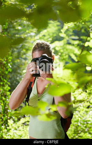 young woman trekking among trees and taking pictures with dslr camera. Vertical shape, front view, waist up - Stock Photo