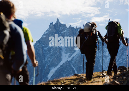 Hikers on Mont Blanc against mountain backdrop of Aiguille du Midi, Chamonix, French Alps, France - Stock Photo