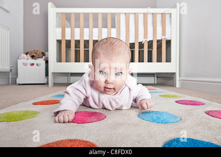 Babys First Crawling Attempts in Nursery - Stock Photo