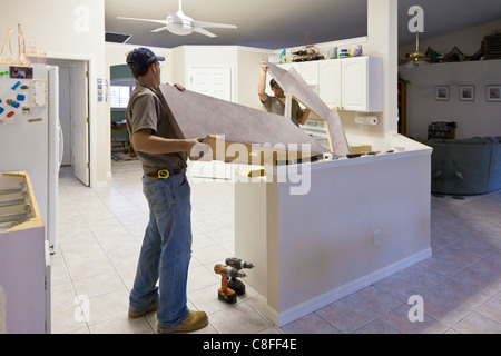 Two men lift Formica counter top from cabinets in modern kitchen during a remodeling project - Stock Photo