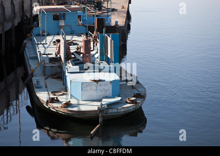 Looking slightly down on a working tug boat moored stern facing camera at jetty with reflection in calm water, river - Stock Photo