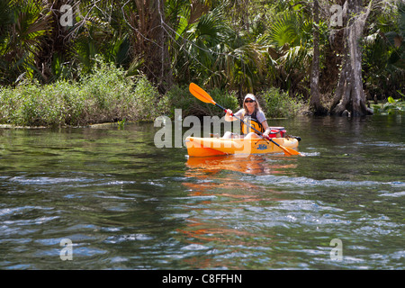 Young woman kayaking in orange kayak on Silver River near Silver Springs State Park in Ocala Florida - Stock Photo